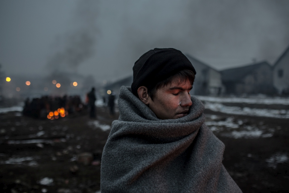 Hazrat, 16, an Afghan refugee, warms himself at a fire behind the main train station of Belgrade. © UNHCR/Daniel Etter