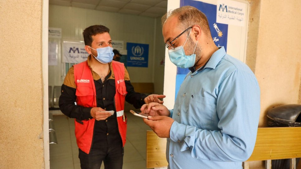 Sameeh, 32, helps a fellow refugee in the camp register to receive the COVID-19 vaccine_UNHCR_Shawkat Alharfosh