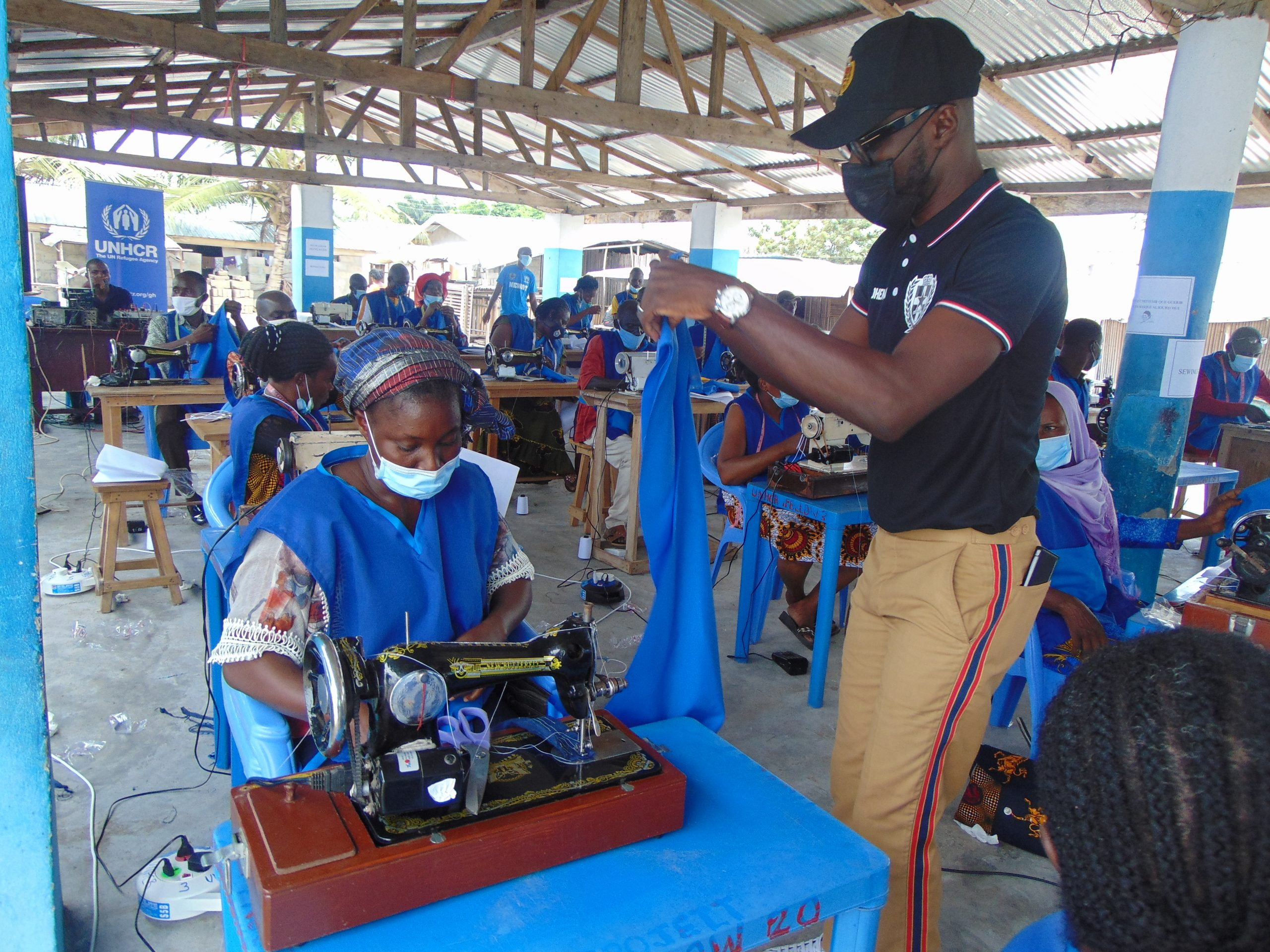 Abrantie taking a refugee through the mask making process. © UNHCR/PFolley