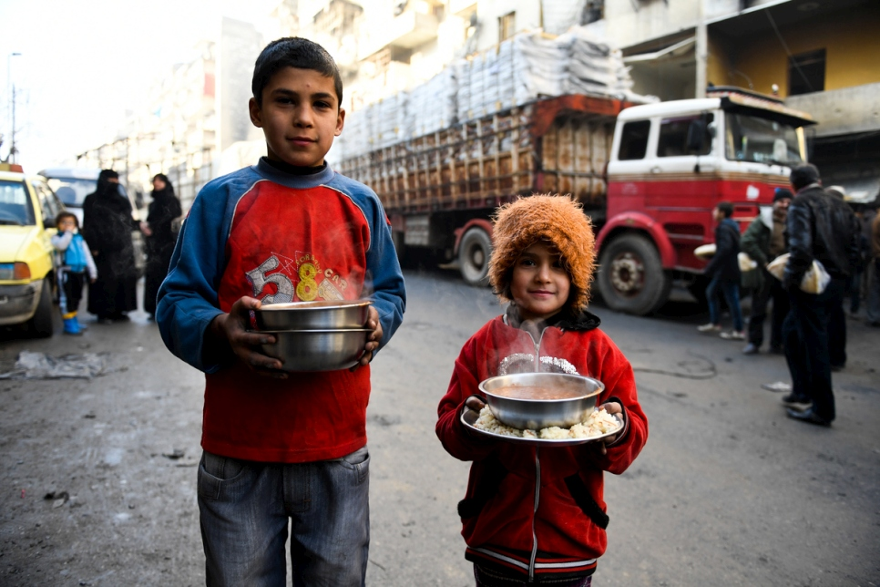 Displaced children carry cooked meals provided by a local charity in the Al-Mashatiyeh neighborhood of east Aleppo, Syria, where UNHCR and its partners are distributing key relief items.