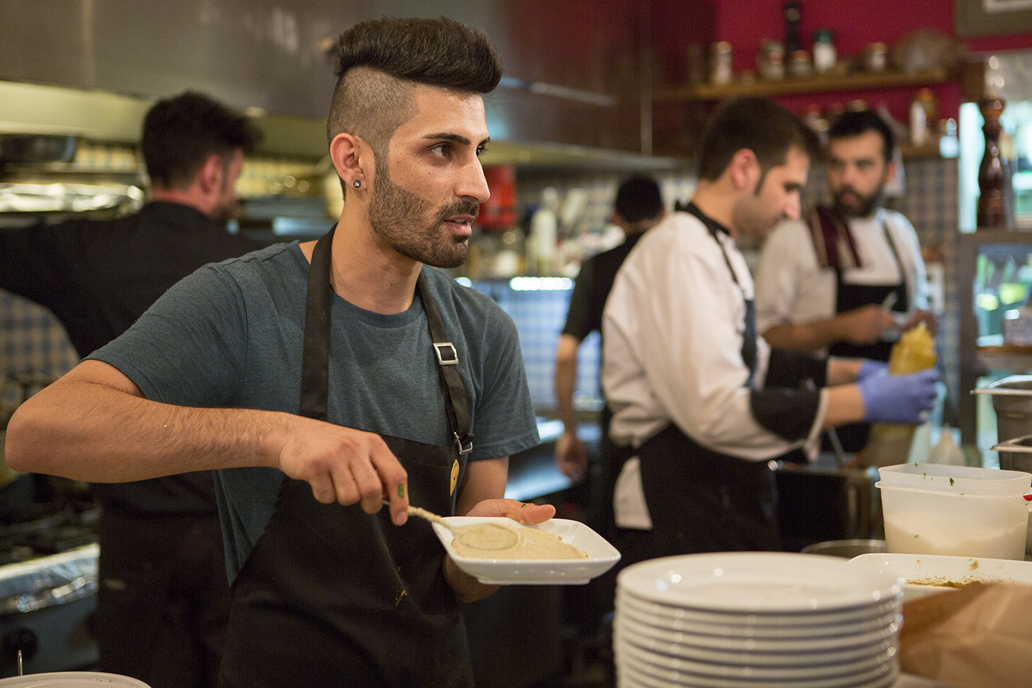 Syrian cook, Barshank Haj Younes, is preparing his dishes in the kitchen of a crowded restaurant in central Athens.