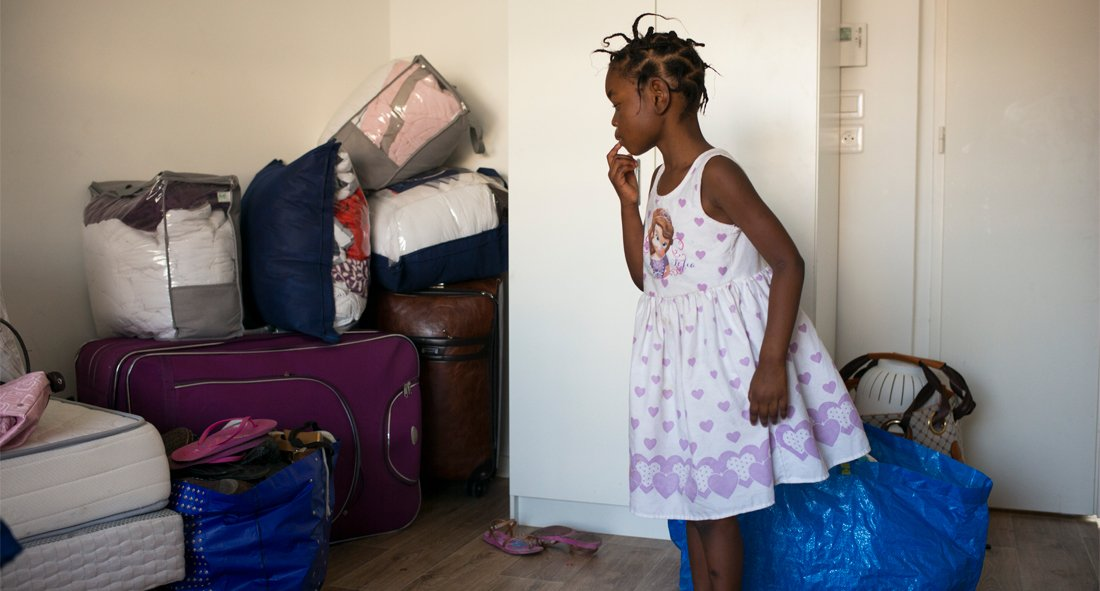 Young girl in a patterned dress stands in a room surrounded by luggage