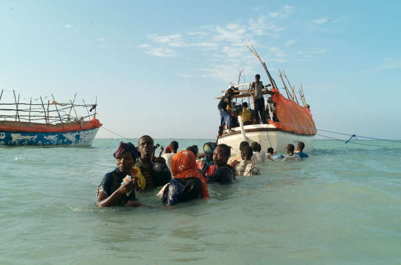 © UNHCR/A.Fazzina Anxious civilians wait to board a smuggler's boat moored off the coast of Somalia.