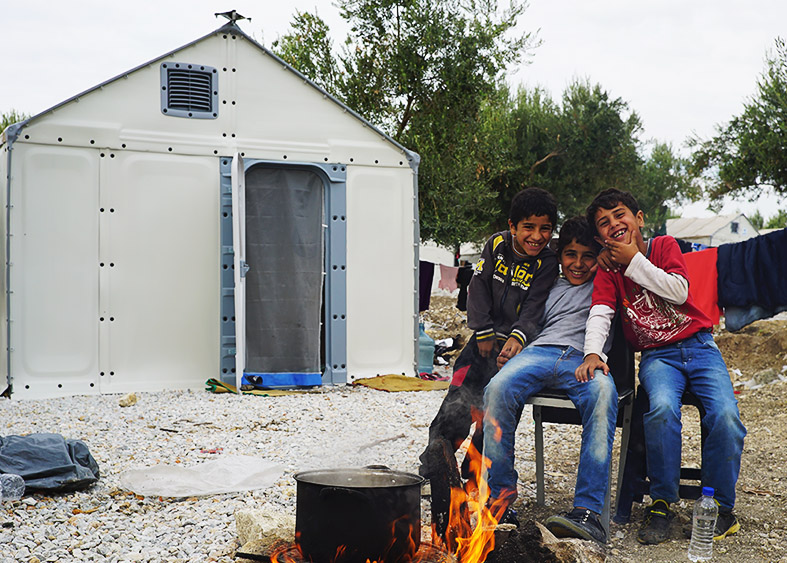 Refugee boys in Lesbos, Greece outside of a Better Shelter Unit.