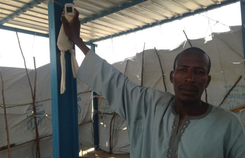 One of the community elders in Sayam Forage, demonstrating the phone and tights communication system.