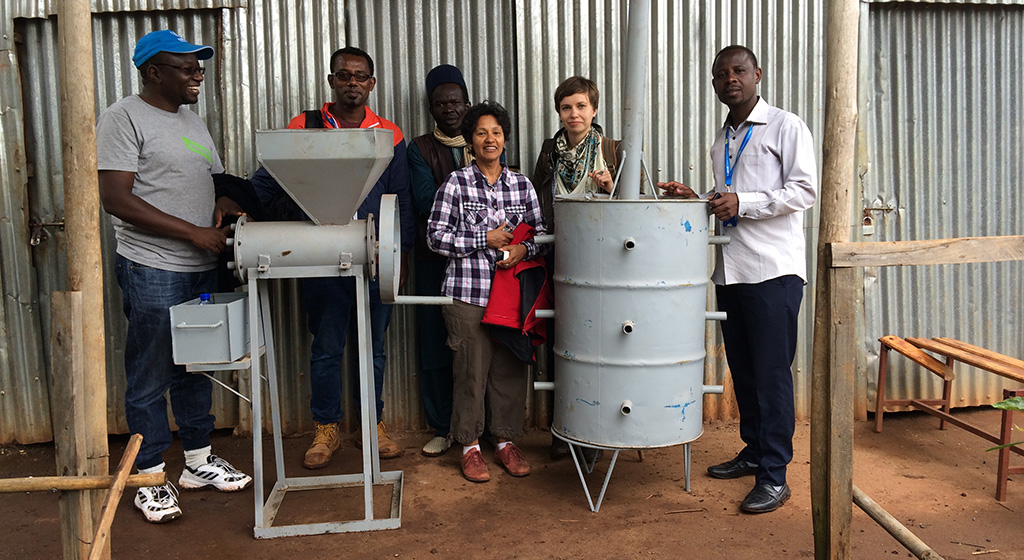 Simeneh (second from left) stands with a prototype of his briquette-making machine.