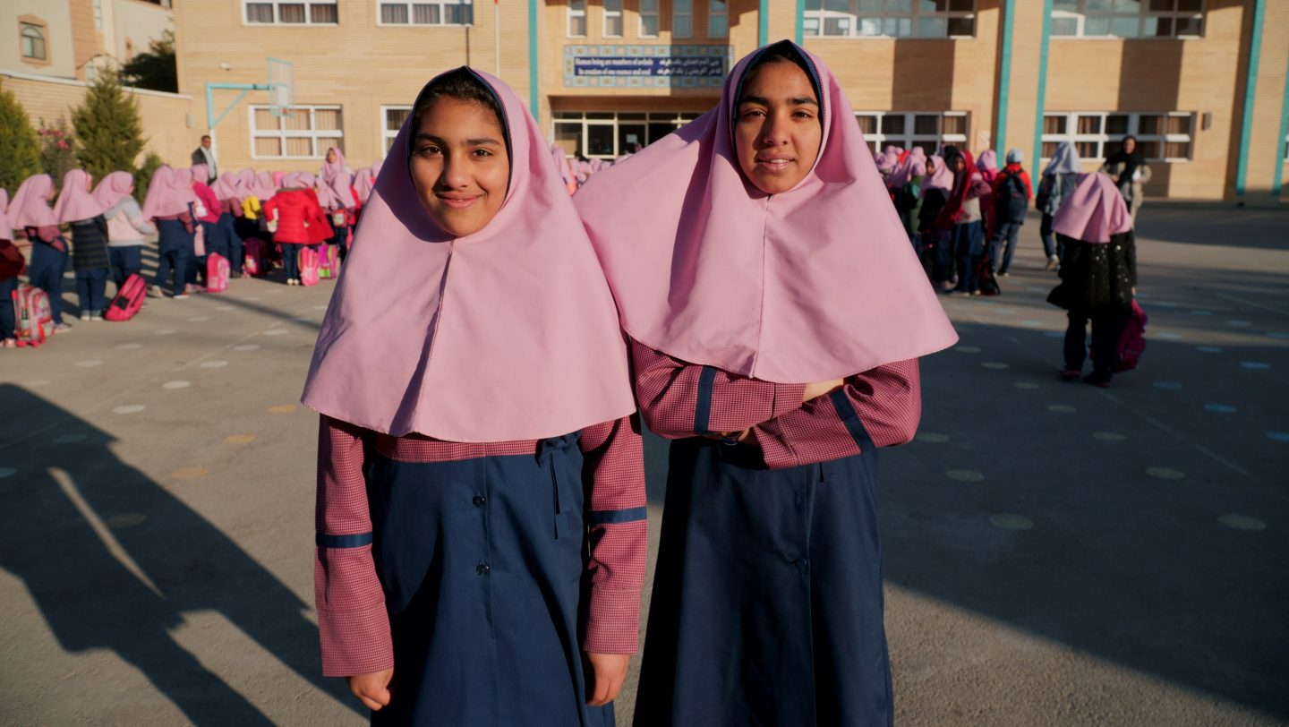 Iran. Parisa and Parimah standing in front of their school building