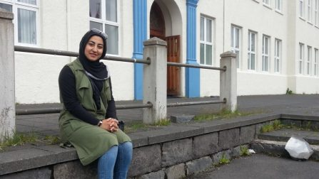 Zahra Mesbah sits outside a building in Iceland
