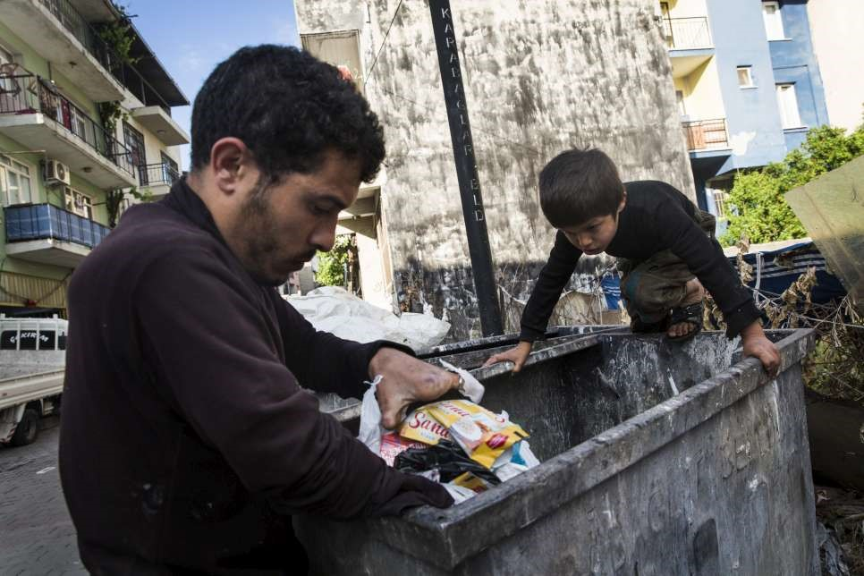 Uday climbs deep into the bins to help his father collect plastic bottles and cans. © UNHCR/Andrew