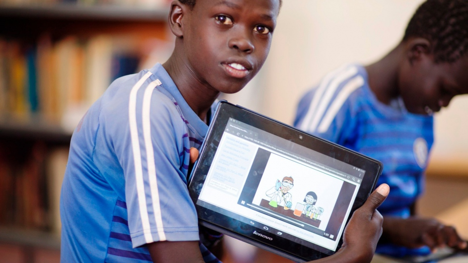 Paul uses a tablet to read at Kakuma refugee camp in Kenya. © UNHCR/Catherine Wachiaya