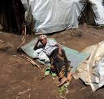 UNHCR / S.Schulman / A woman forced to flee her home village rests outside a shelter in North Kivu province