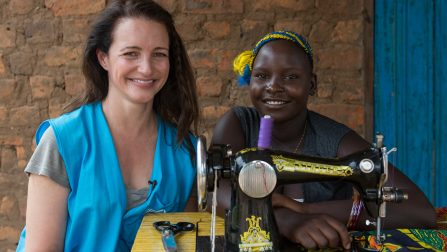 UNHCR High Profile Supporter Kristin Davis spends time with Fiona Taba (18) a South Sudanese refugee who's become a tailor and a fashion designer. Fiona also cultivates a plot of land that was donated by the Ugandan Governmnet at the Rhino Base camps settlement.