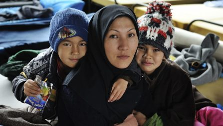 Mother with her son and daughter, from Iran seeking asylum in Austria, in a temporary family accommodation at Asfinag. The Asfinag centre is on the former site of a roadworks company, on the outskirts of Salzburg, a short distance from the border with Germany. Refugees and migrants arrive here directly by bus from the Slovenian border, brought by the Austrian authorities, and most will move on to Germany, and are accommodated in heated tents with camp beds and blankets. For those seeking asylum there are more permanent structures, with family groups separated from single males. Food is provided by volunteers three times a day. ; More than 643,000 refugees and migrants arrived in Europe via the Mediterranean sea this year, including 502,500 in Greece only. Many of the refugees and migrants are desperate to move quickly onwards to Western Europe, fearing that borders ahead of them will close. Although reception capacities have been stepped up the rising numbers has put the Austrian reception system under strain. Many newcomers as well as transiting refugees and migrants are temporarily accommodated in sports- and music halls, former office buildings etc., with those wishing to stay waiting sometimes for weeks to get proper accommodation. With the winter approaching, aid has also been stepped up at the borders. At all border crossings where refugees are arriving or leaving – currently from Slovenia to Austria and from Austria to Germany – large heated tents which can hold up to a few thousand persons have been put up and NGOs, volunteers and authorities are providing basic services.