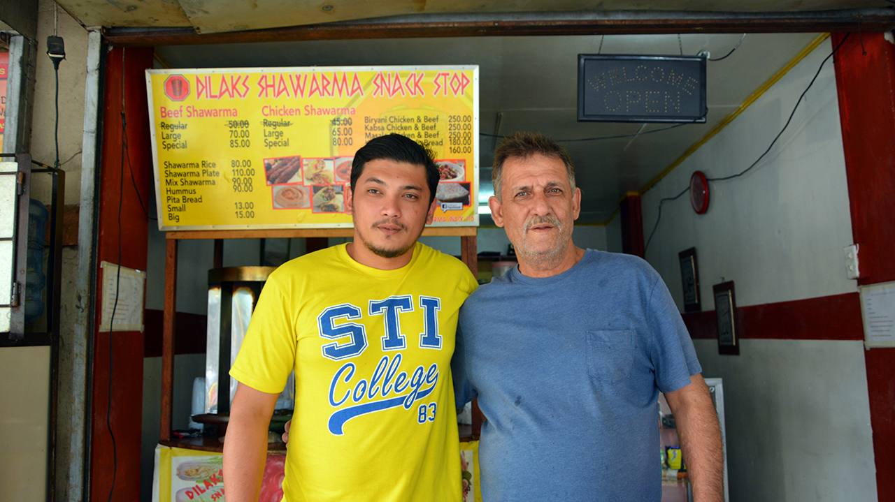 Maher, pictured here with son Khalid, manages their family's shawarma restaurant in Las Piñas. Photo: © UNHCR/A. Gonzales
