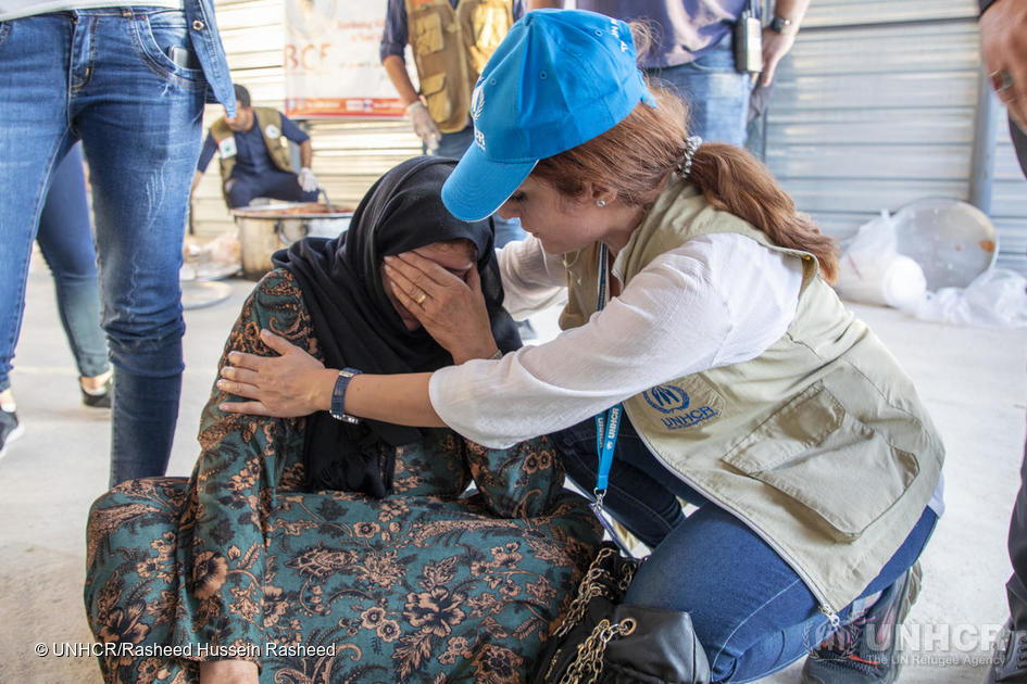 Iraq. UNHCR staff member comforting refugee woman