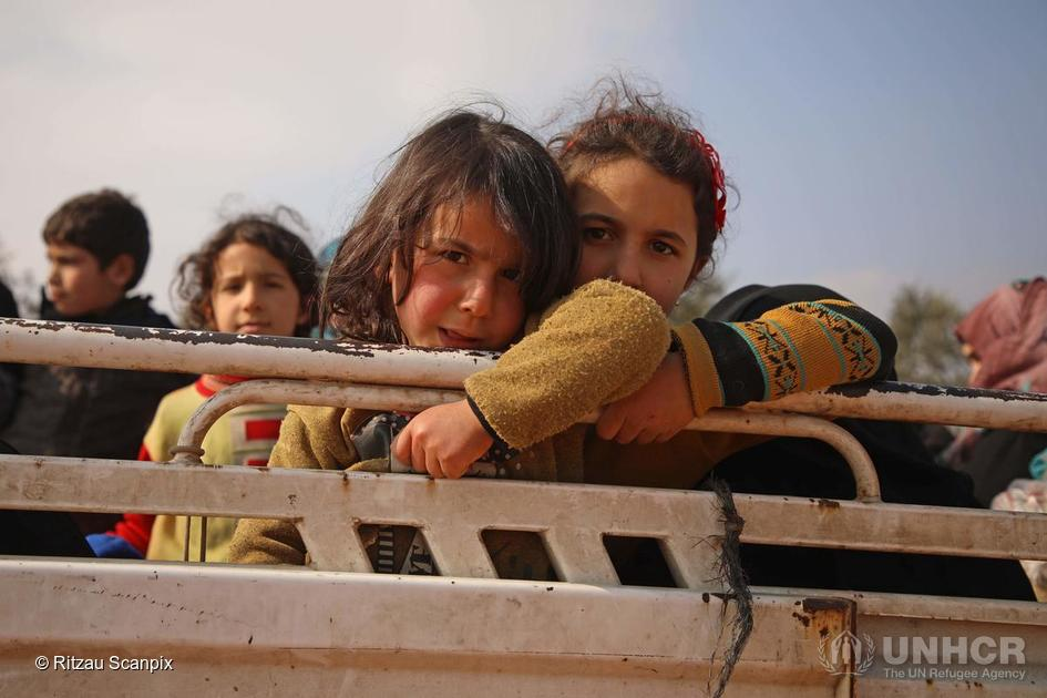 Syria. Displaced Syrian girls stand in the back of a truck parked at a newly-established camp