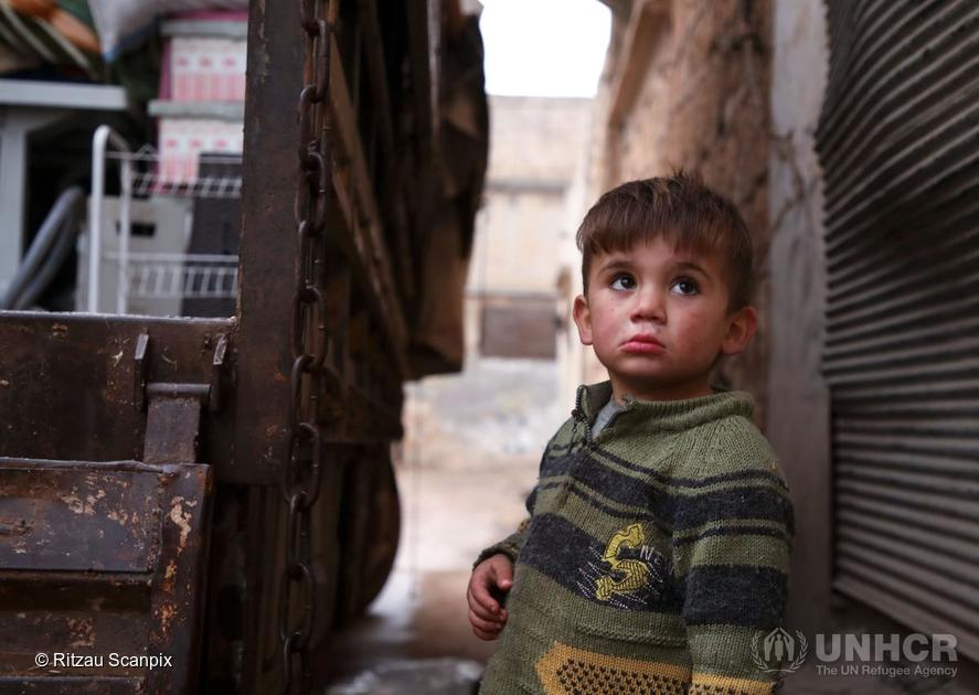 Syria. A Syrian child looks up as relatives load belongings onto a truck as they prepare to leave the town of Binnish