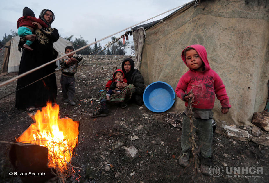 Syria. Displaced Syrian women and children, who fled from southern Idlib, gather around a fire in Afrin