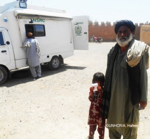 Ghulam's daughter, Parveena, holds the token proving she has applied for her first PoR card at the recently deployed mobile registration van in Chagai district.
