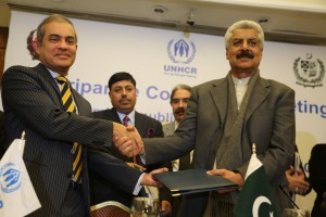 UNHCR's Representative in Pakistan Mr Indrika Ratwatte and Federal Minister for States and Frontier Regions (R) Abdul Quadir Baloch exchanging the signed Tripartite Agreement after the meeting. (C)UNHCR/A.Shahzad