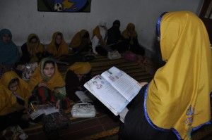 Tahira Naz reading a book in her class room with her classmates in Peshawar. © UNHCR/Qaisar Khan Afridi/Peshawar, Pakistan