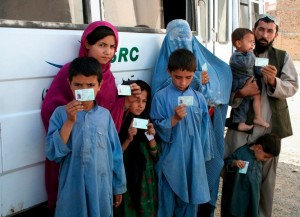 Afghan refugees hold up cards providing proof of registration, in Maach, Pakistan in 2008. A new pilot programme that began this week is issuing citizen cards to undocumented Afghans in Pakistan.   © UNHCR/DAKhan