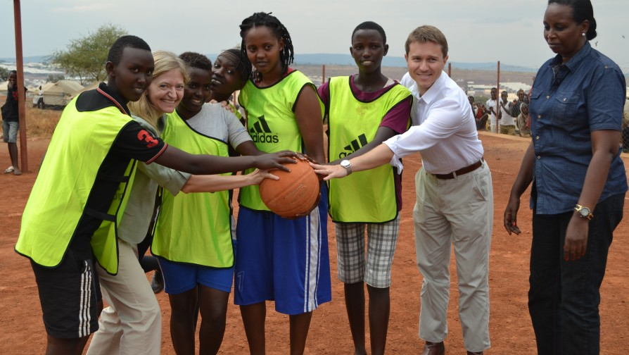 US envoy to Rwanda, Erica J. Barks-Ruggle, and British High Commissioner to Rwanda, William Gelling pose for a baksetball team group photo with refugees at the camp [Photo/ UNHCR - Eugene Sibomana]
