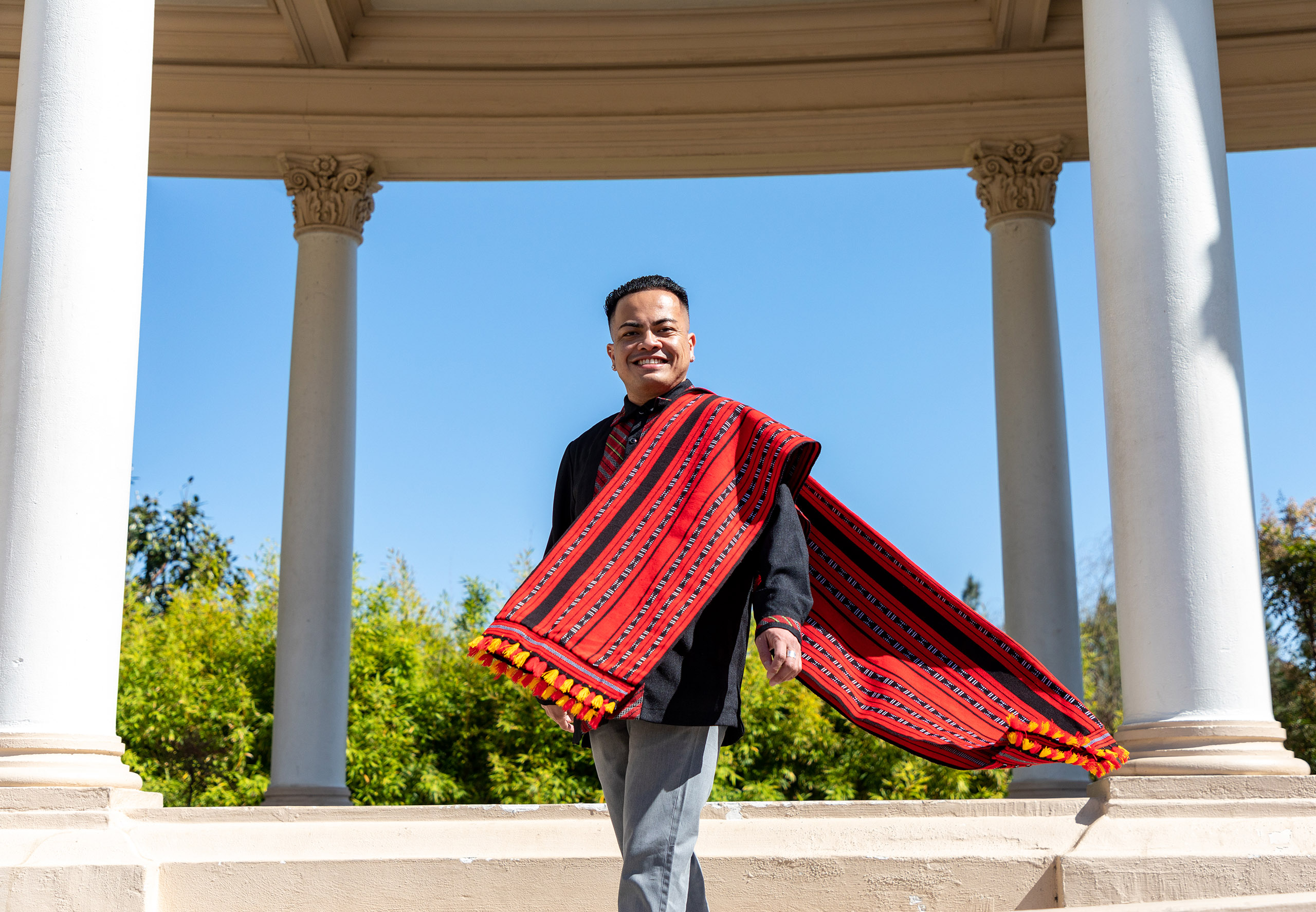 A Philippino-American man with a long, red woven scarf stands among several stone columns under a blue sky.