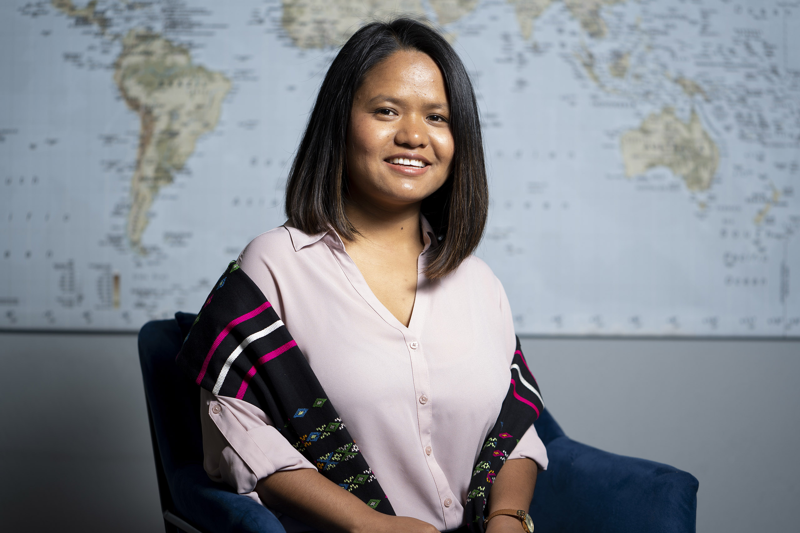 Burmese-American woman in pink blouse seated in front of a world map.
