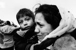 An Afghan mother hugs her child and weeps with relief on arrival on th...