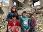 Zahida's four daughters pose by the ruins of their home in Souran, Syr...