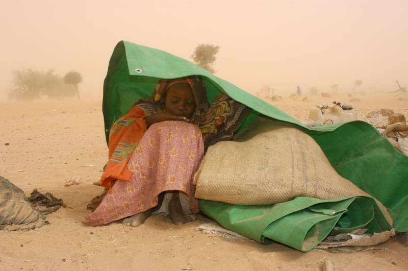 A Sudanese refugee seeks shelter from a sandstorm near the Chadian border town of Tine. (February 7, 2004)