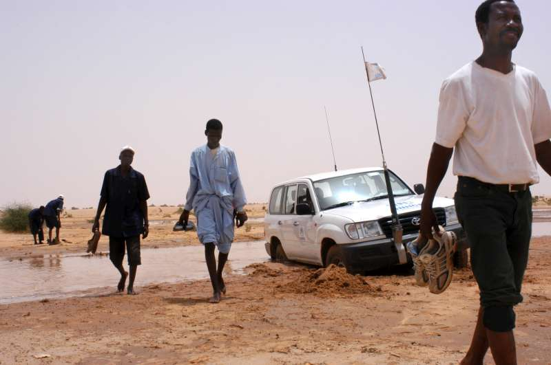 UNHCR and Red Cross workers continue by foot across the seasonal riverbed where a UNHCR vehicle got stuck. It took four hours for two cars and a truck to liberate the trapped vehicle. (July 16, 2004)