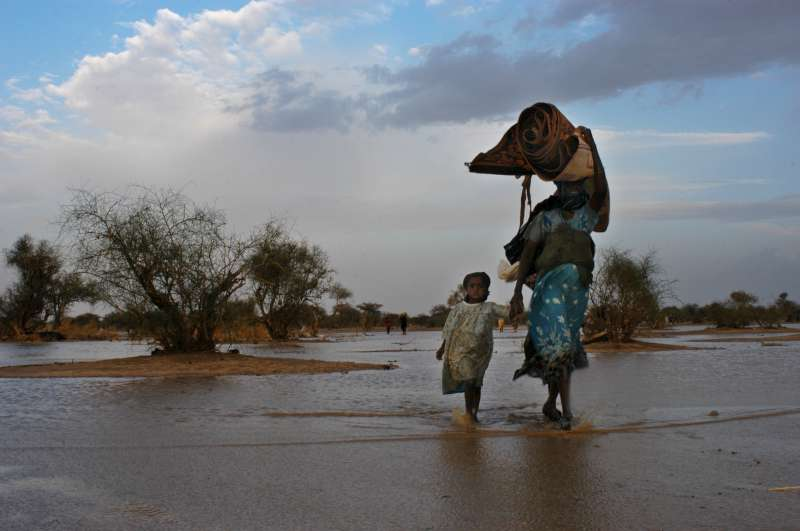 A refugee family carrying their belongings out of the water after their makeshift shelter was flooded when the first heavy rains near Bahai swelled the seasonal riverbed. The flooded-out refugees were immediately transferred to a new camp that had just opened to receive them. (July 14, 2004)