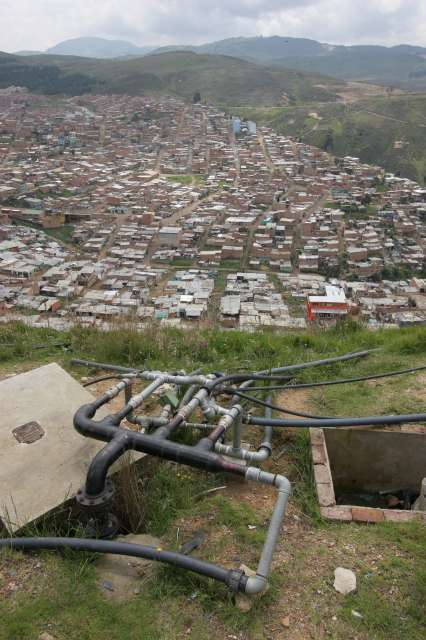 Services in the <em>barrios</em> are usually sub-standard at best. Here, in Los Altos de la Florida, tubes running from a big tank secured at the top of the hill bring water to hundreds of houses, but only for a few hours each day.