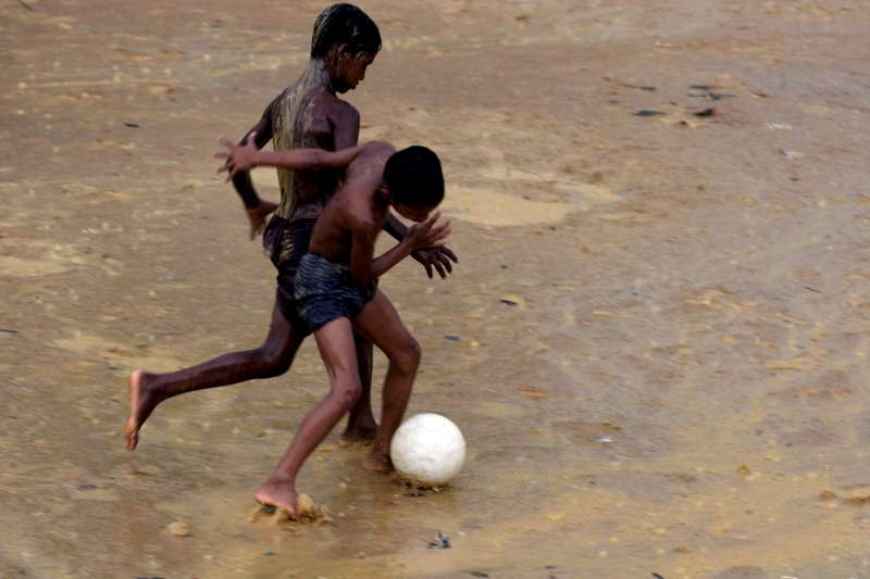 Children make up about 65 percent of the population at the Nayapara camp, but there is little for them to do. Here boys play football in the rain.
