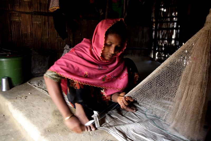 A woman weaves fishing nets to sell in the local market, Nayapara camp, Cox's Bazar.