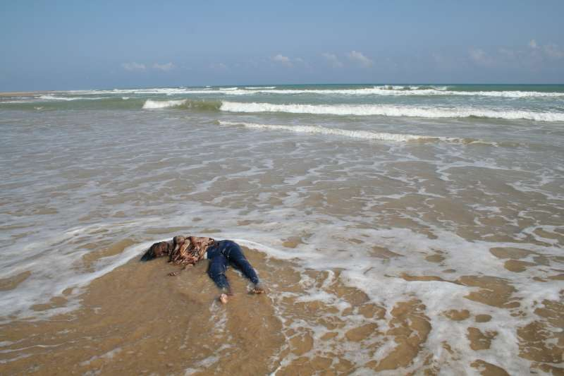 The body of a Somali woman washes up on the shores of South Yemen. In order to avoid detection, smugglers often force passengers off their boats and into the shark-infested waters far from shore.