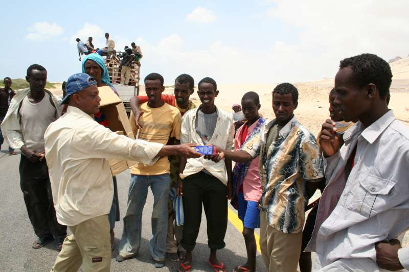 Workers from a Yemeni non-governmental organisation hand out food before transporting newly arrived Somalis and Ethiopians to the Mayfa'a reception centre.