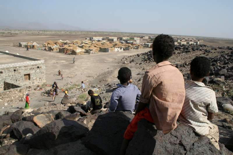 Young Somalis and Ethiopians perch on a hill overlooking the part of the Kharaz refugee camp that houses new arrivals.