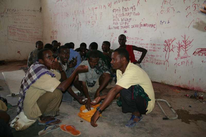 Somali and Ethiopian refugees and migrants wait in a room in the Obock detention centre.
