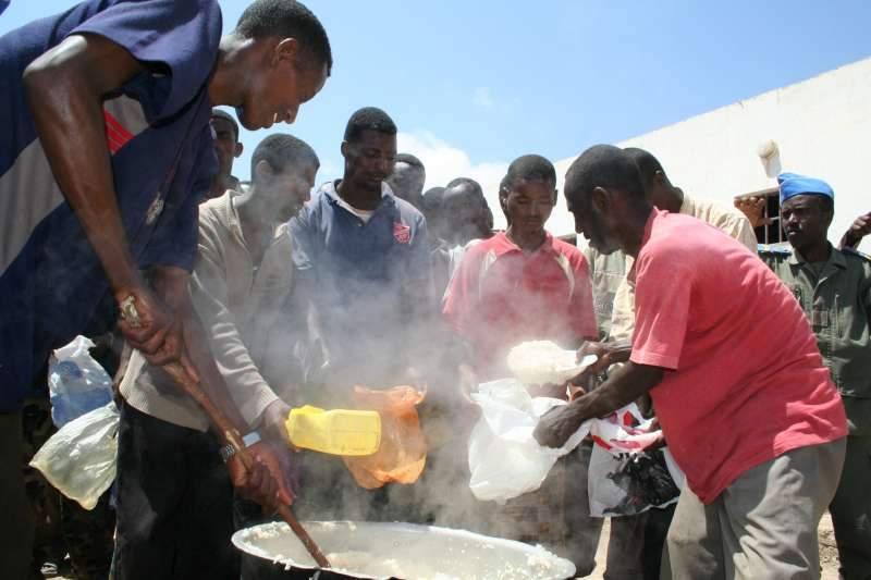 Detained Somalis and Ethiopians prepare a meal at the Obock detention centre.