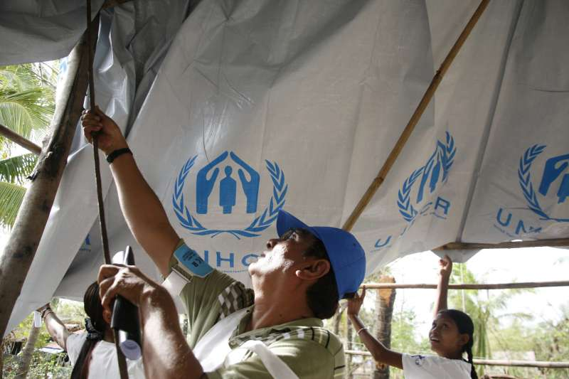 UNHCR staff help a family build a temporary roof with plastic sheeting after their home was destroyed by Cyclone Nargis.