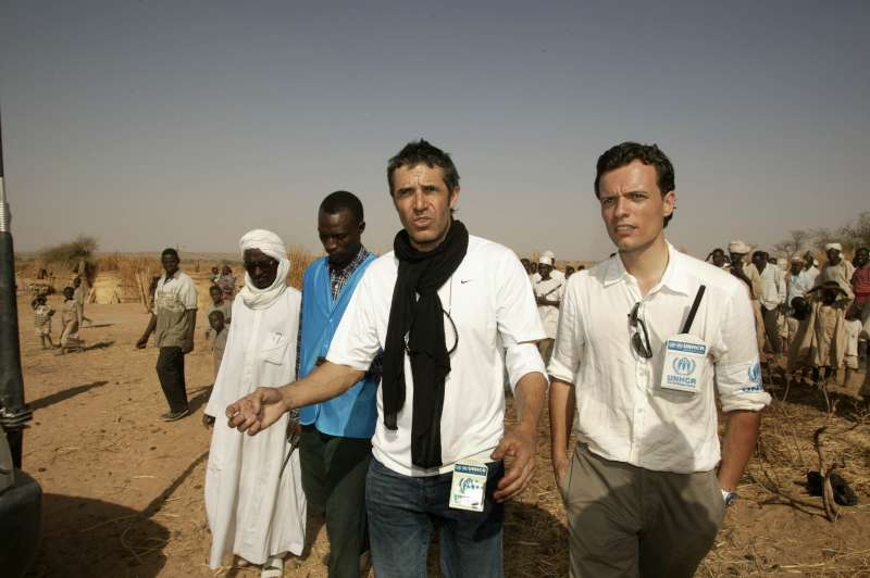 A UNHCR programme officer explains to UNHCR Goodwill Ambassador Julien Clerc how the UN refugee agency cares for Sudanese refugees from the Darfur region once they arrive at the temporary site of Mahamata in eastern Chad. March 2, 2004.