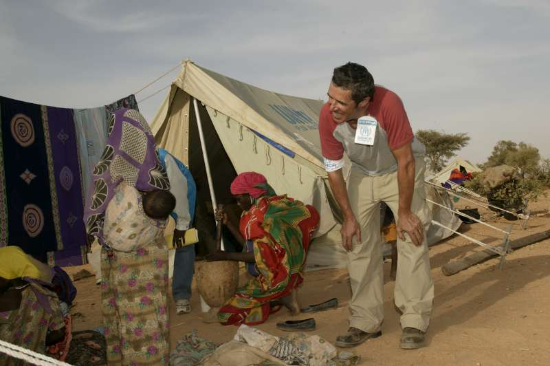 UNHCR Goodwill Ambassador Julien Clerc chats with a Sudanese refugee girl in Kounoungo camp, eastern Chad. March 3, 2004.