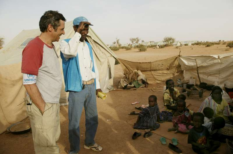 UNHCR Goodwill Ambassador Julien Clerc talking with a Sudanese refugee family in Kounoungo camp, eastern Chad. March 3, 2004.