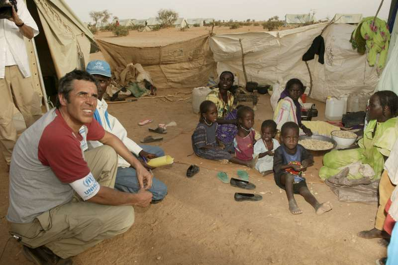 UNHCR Goodwill Ambassador Julien Clerc listens to the plight of a Sudanese refugee family in Kounoungo camp, eastern Chad. March 3, 2004.