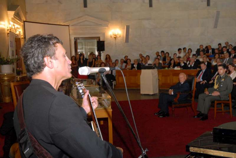 UNHCR Goodwill Ambassador George Dalaras plays guitar and sings to dignitaries attending his induction ceremony in Athens on October 5, 2006.