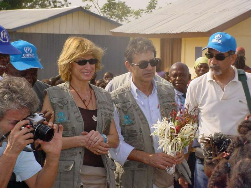 Goodwill Ambassador George Dalaras (with flowers), his wife Anna and UNHCR staff at a welcoming ceremony in a Sierra Leone refugee camp.