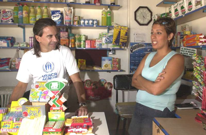 UNHCR Goodwill Ambassador Osvaldo Laport chats to a refugee in Argentina who received a small loan from UNHCR to help set up her own shop.